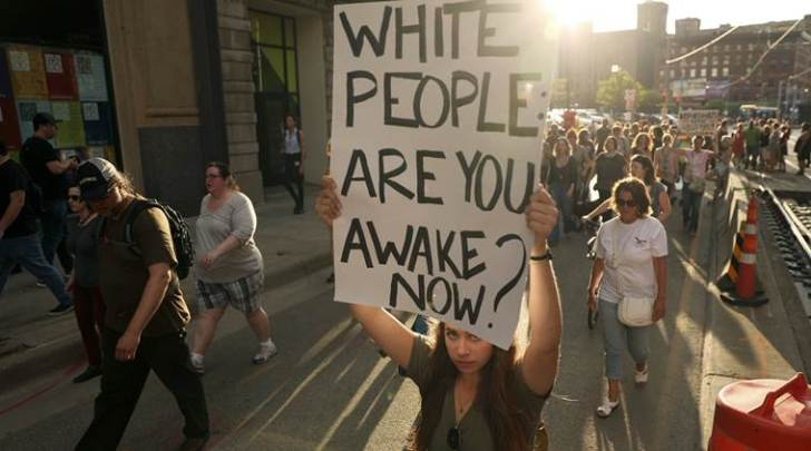 Protesters carry signs as they march against police violence from Loring Park to City Hall, Friday, July 21, 2017, in Minneapolis, Minn.  (Anthony Souffle/Star Tribune via AP)