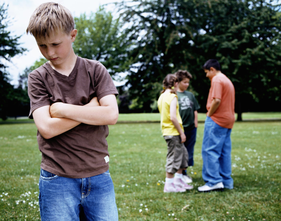 Boy (9-11) standing in park, arms crossed, group (10-12) in background
