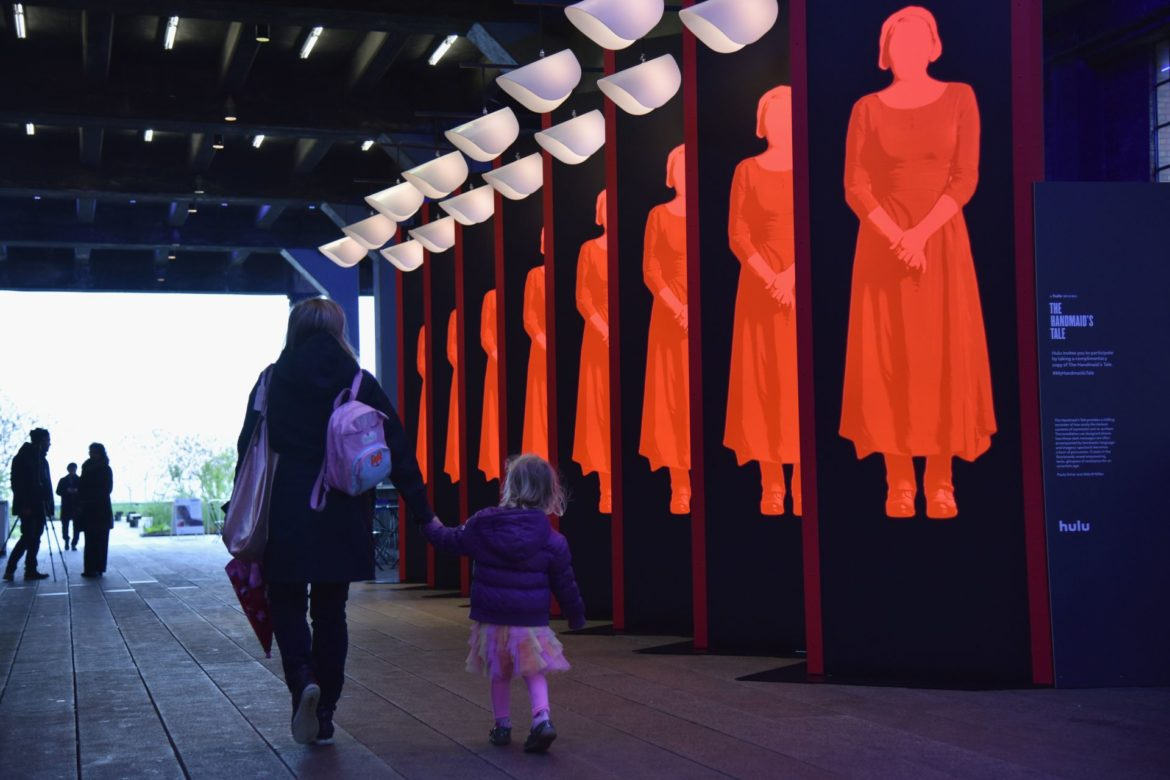 NEW YORK, NY - APRIL 26:  Guest interact with an art installation, designed by Paula Scher and Abbott Miller, and book giveaway celebrating Hulu's 'The Handmaid's Tale' opens on the High Line on April 26, 2017 in New York City.  (Photo by Bryan Bedder/Getty Images for Hulu)